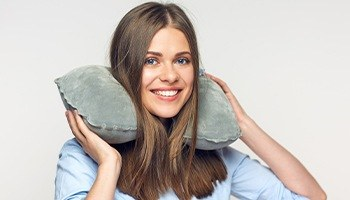 A young female smiling while holding onto a neck pillow for comfort
