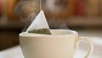 A person dipping a tea bag into a hot cup of water