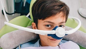 A young boy with a nasal mask preparing to receive nitrous oxide