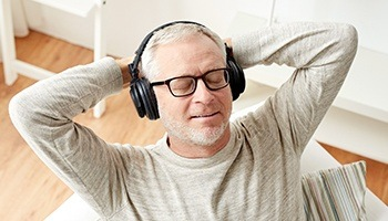 A middle-aged gentleman sitting back with his eyes closed wearing noise-canceling Bluetooth headphones