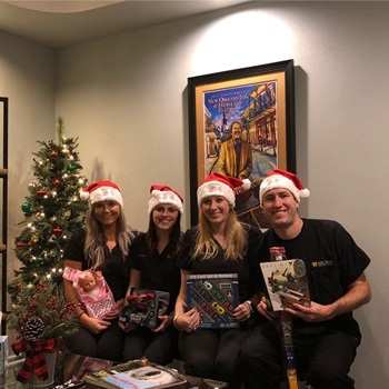 Team members holding toy drive gifts