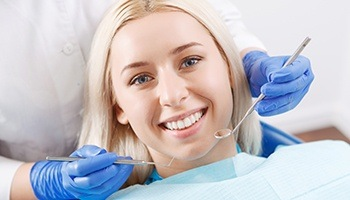Woman smiling happily during dental examination