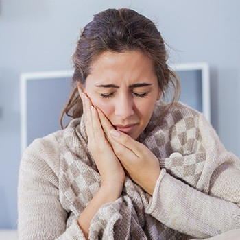 Woman wearing sweater grasping cheek in pain