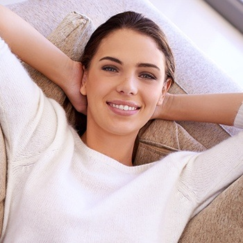 Woman laying on couch with arms behind head