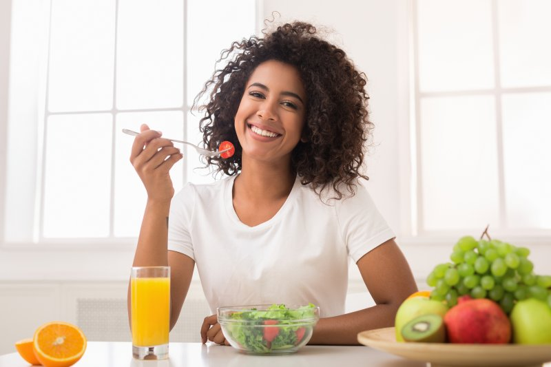 Woman smiling while eating a salad